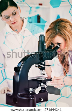 Science and medical graphic against blond scientist looking through a microscope with her assistant