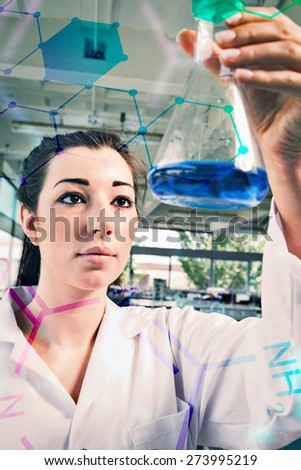 Science and medical graphic against portrait of a brunette looking at a blue liquid - stock photo