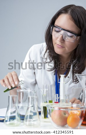 Science and Medicine Concepts. Portrait of Female Lab Staff Dealing With Flasks and Its Substances in Laboratory Environment. Vertical Image Orientation