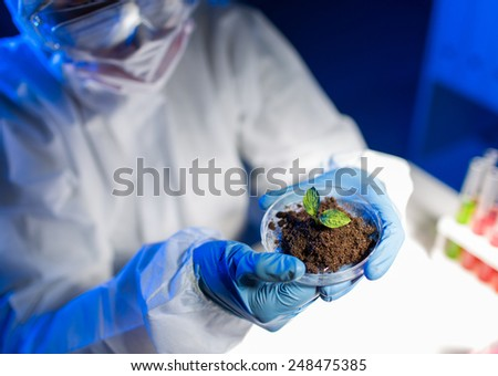 science, biology, ecology, research and people concept - close up of young female scientist holding petri dish with plant and soil sample in bio laboratory - stock photo