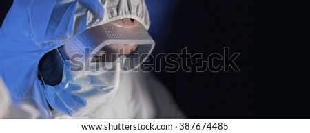 science, chemistry, biology, medicine and people concept - close up of scientist face in goggles and protective mask at chemical laboratory over dark background - stock photo