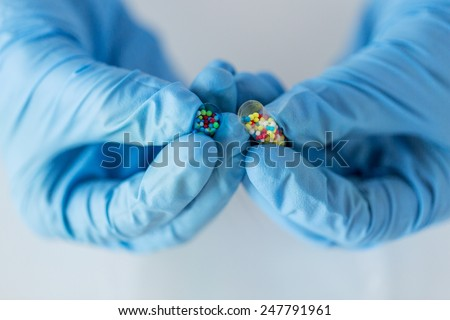 science, chemistry, biology, medicine and people concept - close up of scientist or doctor hands holding and pouring pill content into petri dish in laboratory - stock photo