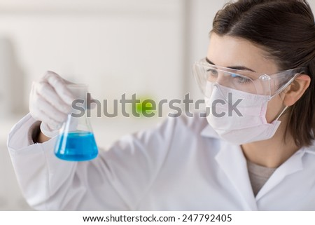 science, chemistry, biology, medicine and people concept - close up of young female scientist with flask making test or research in clinical laboratory - stock photo