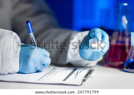 science, chemistry, medicine and people concept - close up of young scientist with chemical sample taking notes on clipboard and making test or research in laboratory - stock photo
