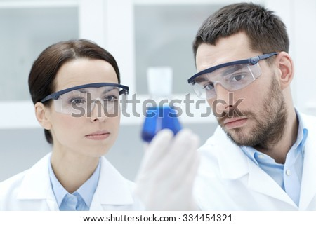 science, chemistry, research, biology and people concept - young scientists holding flask with medicine or chemical in clinical laboratory - stock photo