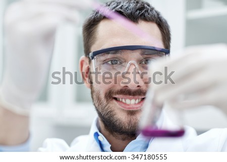 science, chemistry, technology, biology and people concept - young scientist mixing reagents from glass flasks and making test or research in clinical laboratory - stock photo