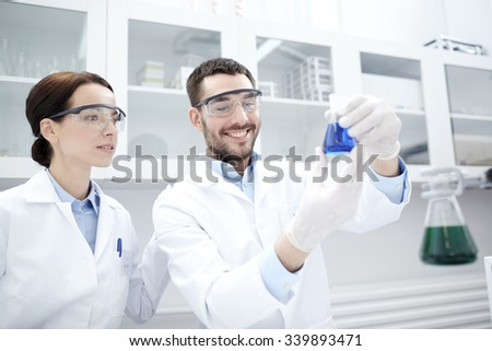 science, chemistry, technology, biology and people concept - young scientists holding flask with reagents and making test or research in clinical laboratory - stock photo