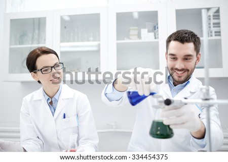 science, chemistry, technology, biology and people concept - young scientists mixing reagents from glass flasks and making test or research in clinical laboratory - stock photo