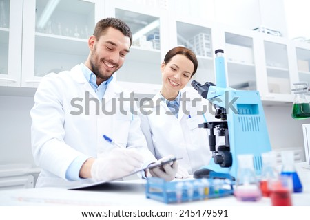 science, chemistry, technology, biology and people concept - young scientists with microscope making test or research in clinical laboratory and taking notes - stock photo