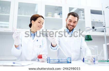 science, chemistry, technology, biology and people concept - young scientists with pipette and flask making test or research in clinical laboratory - stock photo