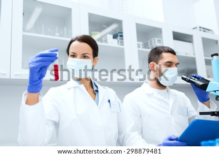 science, chemistry, technology, biology and people concept - young scientists with test tube and microscope making research in clinical laboratory - stock photo