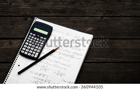 Science concept - handheld calculator and pencil over a sheet of paper with maths-formulas lying on a dark wooden desk - stock photo