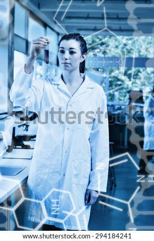 Science graphic against portrait of a beautiful scientist looking at a test tube - stock photo