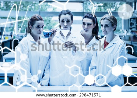Science graphic against science students pouring liquid in a flask - stock photo