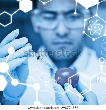Science graphic against scientific researcher injecting a tomato at the lab - stock photo