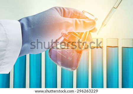 science hand and laboratory test tubes - stock photo