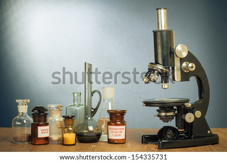 Science microscope and old laboratory glass on table vintage photo - stock photo