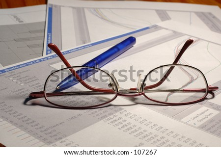 Science reports with graphs on the table with blue pen and womans glasses.