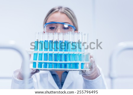 Science student holding tray of test tubes at the university - stock photo
