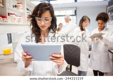 Science student looking at tablet pc in the lab at the university - stock photo