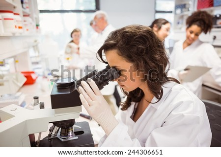 Science student looking through microscope in the lab at the university - stock photo