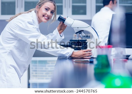 Science student working with microscope in the lab at the university - stock photo