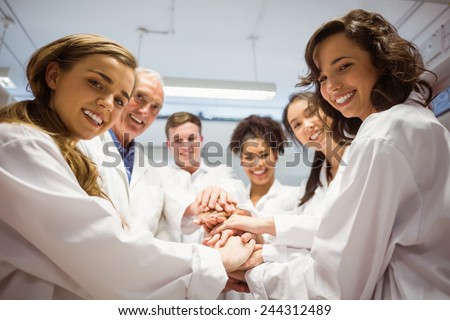 Science students and lecturer putting hands together at the university - stock photo
