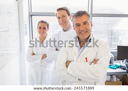Science students and lecturer smiling at camera at the laboratory - stock photo