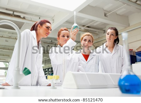 Science students looking at a liquid in a flask in a laboratory - stock photo