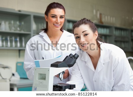 Science students posing with a microspcope in a laboratory - stock photo