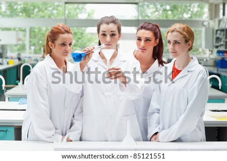 Science students pouring liquid in a flask in a laboratory - stock photo