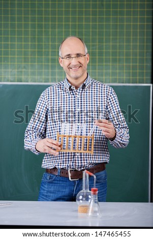 Science teacher conducting an experiment for the class smiling as he stands in front of the blackboard holding a rack of test tubes - stock photo