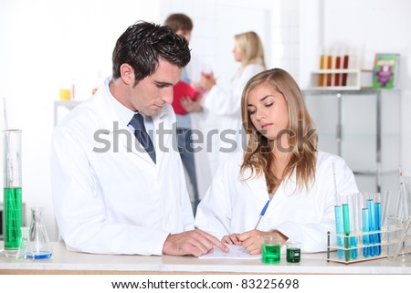 Science teacher helping student in laboratory - stock photo
