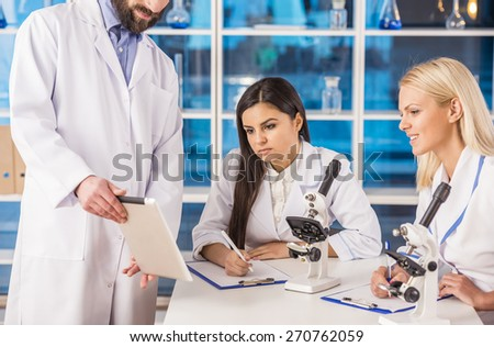 Science team are looking at the tablet while working in a laboratory. - stock photo