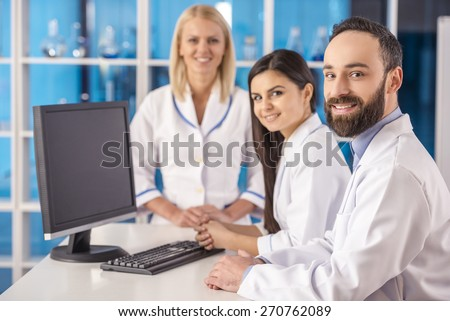 Science team working with computer pc and looking at camera in a laboratory. - stock photo