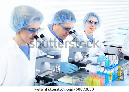 Science team working with microscopes at  laboratory - stock photo