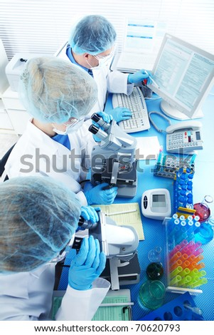 Science team working with microscopes at  laboratory