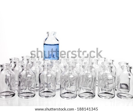 Science Vials in Rows with one vial sitting on top of the others filled with a light blue liquid. - stock photo