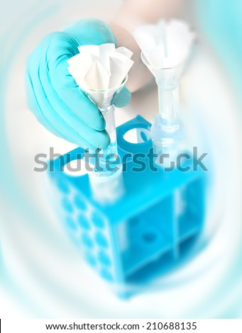Scientific background, gloved hand holds a funnel with paper filter, text space