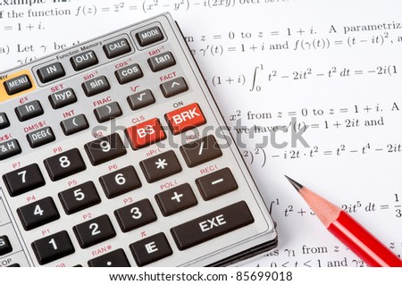 Scientific calculator and a red pencil on top of a sheet of paper with maths formulas - stock photo
