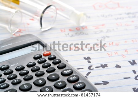 Scientific calculator with functions and  laboratory glass cylinders with test tube over notepad with hand written chemical formulas and applied results during an experiment in a science research lab