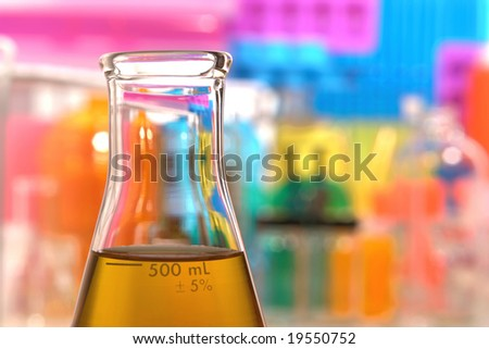 Scientific laboratory glass conical Erlenmeyer flask filled with amber chemical liquid for a chemistry experiment in a science research lab - stock photo