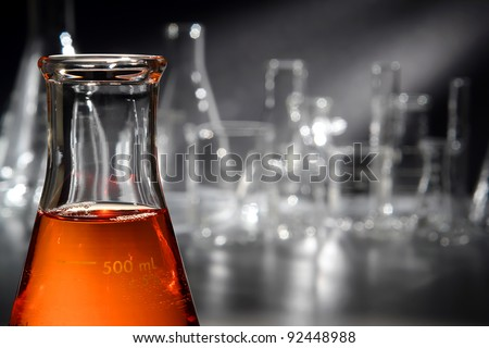 Scientific laboratory glass conical Erlenmeyer flask filled with amber orange chemical liquid for a chemistry experiment in a science research lab - stock photo