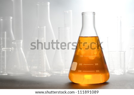 Scientific laboratory glass conical Erlenmeyer flask filled with amber orange chemical liquid with glassware equipment in fog or smoke for a chemistry experiment in a science research lab - stock photo