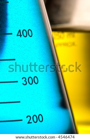 Scientific laboratory glass conical Erlenmeyer flask filled with blue chemical liquid and beaker with yellow solution for a chemistry experiment in a science research lab - stock photo