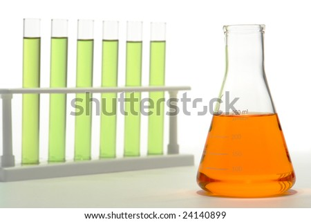 Scientific laboratory glass conical Erlenmeyer flask filled with orange chemical liquid and test tubes on a rack for a chemistry experiment in a science research lab - stock photo