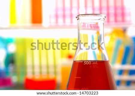 Scientific laboratory glass conical Erlenmeyer flask filled with red chemical liquid for a chemistry experiment in a science research lab - stock photo