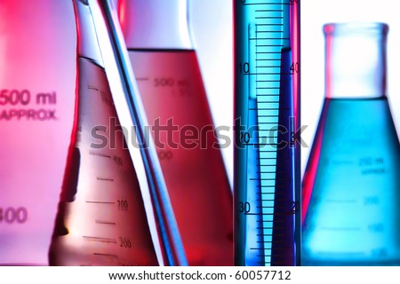Scientific laboratory graduated cylinder filled with blue liquid and conical Erlenmeyer flasks full of aqua and pink chemical solution for an experiment in a science research lab - stock photo