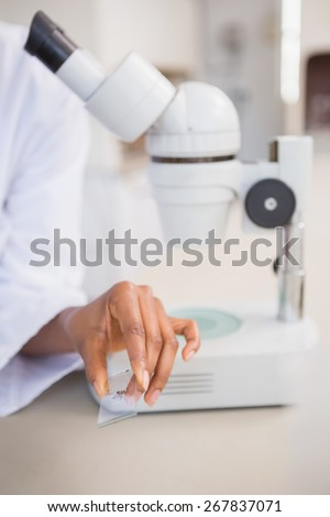Scientist analyzing slide of sample in laboratory - stock photo