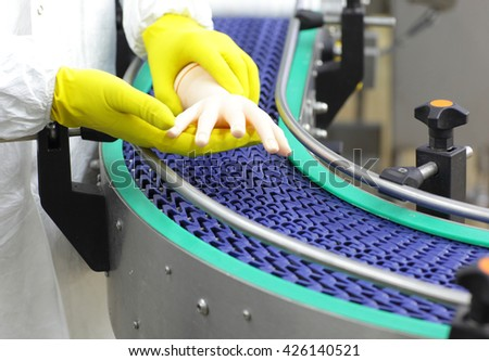 scientist at conveyor belt controlling  artificial bionic hand . a concept of spare body parts mass production - stock photo